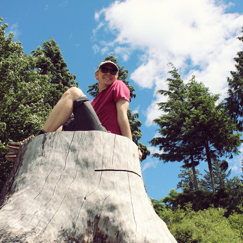A picture of Peter sitting on a stump with sunglasses on and trees in the background